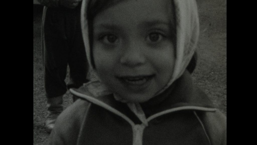 A screen cap of a home movie featuring a little girl in a cap